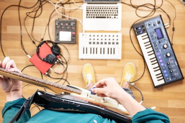 Junge frau, die e-gitarre im proberaum aufnimmt, aus sicht. draufsicht der produzentin im heimstudio, die gitarre und elektronische instrumente spielt.