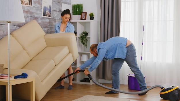Junge frau, die ehemann hilft, den staub unter dem sofa zu säubern.