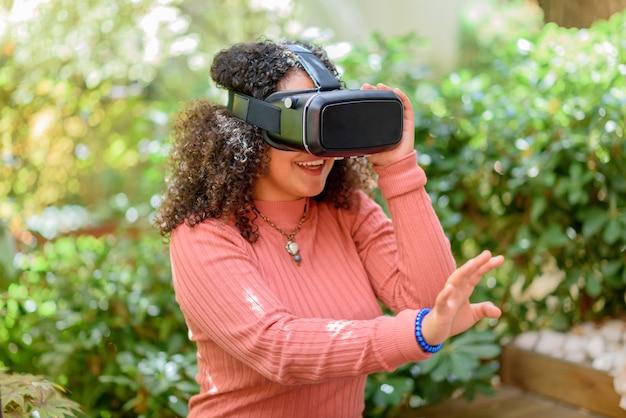 Junge frau, die ein 3d-virtual-reality-headset im freien auf einer terrasse verwendet und mit ihrer hand gestikuliert, während sie in ihre simulierte umgebung vor einem grünen hintergrund eintaucht
