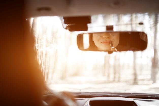 Junge frau, die ein auto fährt. sie bemalt ihre lippen mit lippenstift im rückspiegel.