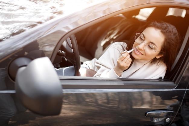 Junge frau, die ein auto fährt. sie malt ihre lippen mit lippenstift im rückspiegel