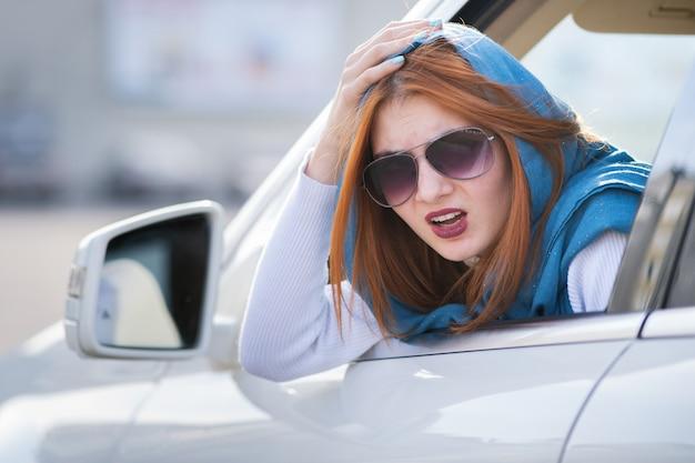 Junge frau, die ein auto rückwärts fährt. mädchen mit lustigem gesichtsausdruck, während sie einem hinteren fahrzeug einen kotflügelschaden anrichtete.