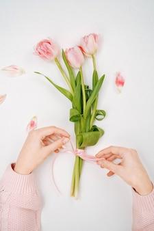 Junge frau, die ein band an einem strauß rosa tulpen bindet. ansicht von oben, weißer hintergrund, textkopierraum.