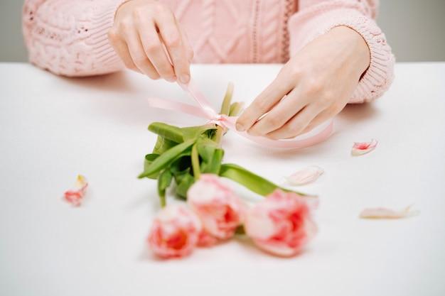 Junge frau, die ein band an einem strauß rosa tulpen bindet. selektiver fokus, weißer hintergrund, textkopierraum.