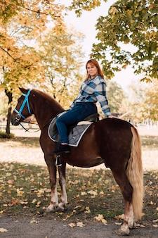 Junge frau, die ein braunes pferd reitet, das an einem sonnigen tag eine halbe drehung posiert, spaziert im herbstpark