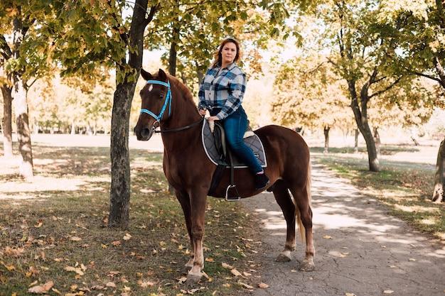 Junge frau, die ein braunes pferd reitet, geht an einem sonnigen tag im herbstpark spazieren