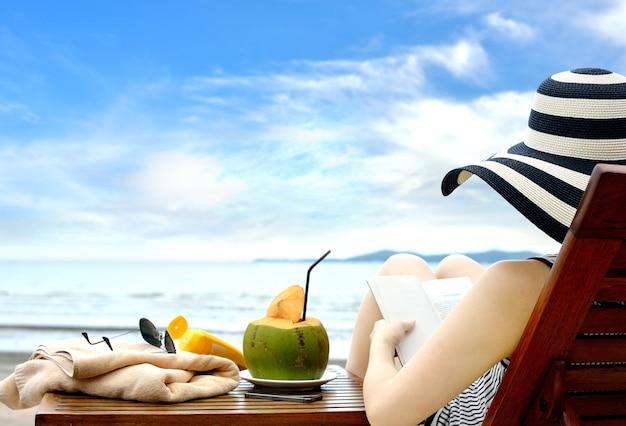 Junge frau, die ein buch am strand liest