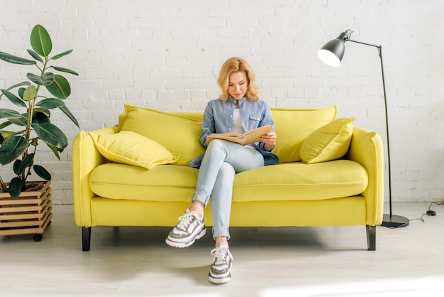 Junge frau, die ein buch auf gemütlicher gelber couch liest