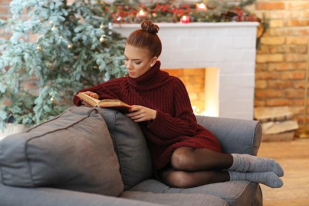 Junge frau, die ein buch im sofa liest