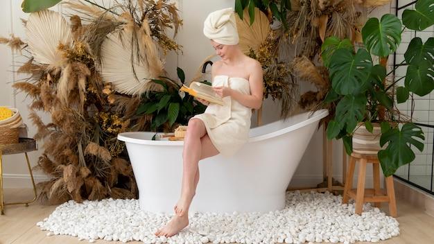 Junge frau, die ein buch liest, nachdem sie ein bad genommen hat