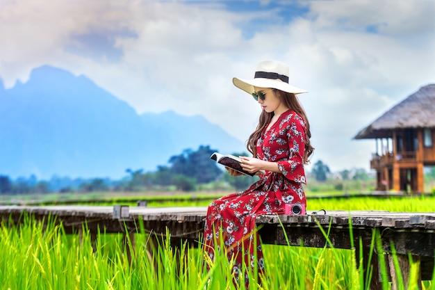 Junge frau, die ein buch liest und auf hölzernem weg mit grünem reisfeld in vang vieng, laos sitzt.