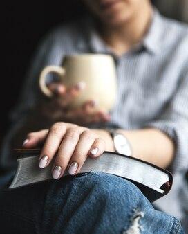 Junge frau, die ein buch liest und tasse tee oder kaffee hält.