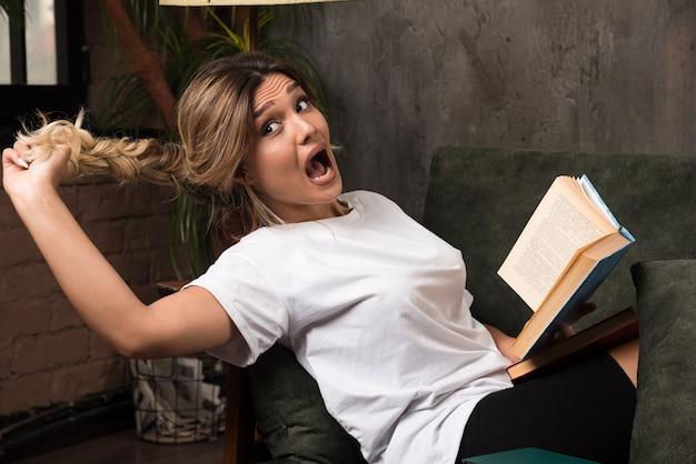 Junge frau, die ein buch liest, während sie ihre haare auf der couch zieht.