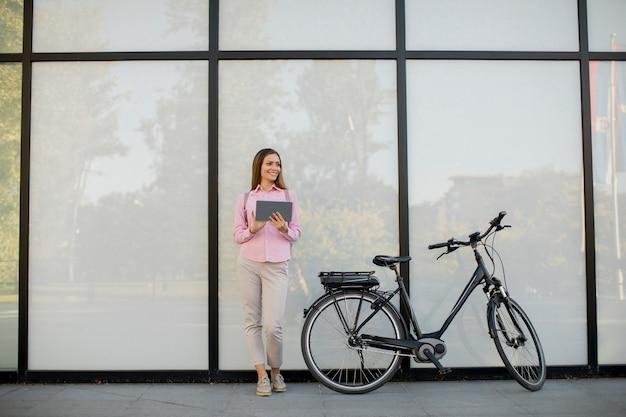 Junge frau, die ein elektrisches fahrrad bereitsteht und digitale tablette in der städtischen umwelt verwendet