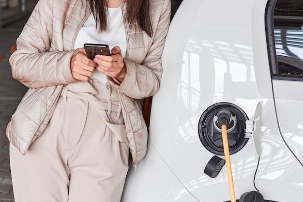 Junge frau, die ein elektroauto an der öffentlichen ladestation auflädt und mit einem mobiltelefon zahlt. innovatives umweltfreundliches fahrzeug.