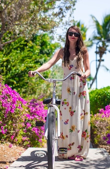 Junge frau, die ein fahrrad auf tropisches erholungsort reitet
