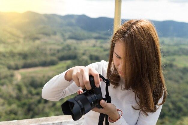 Junge frau, die ein foto am berg macht