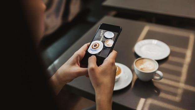 Junge frau, die ein foto von ihrem kaffee macht