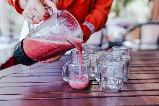 Junge frau, die ein gesundes rezept der verschiedenen früchte, der wassermelone, der orange und der brombeeren gießt. mit einem mixer. selbstgemacht, drinnen, gesunder lebensstil