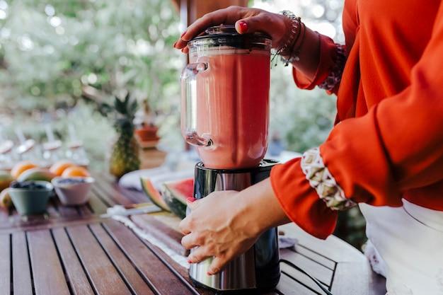 Junge frau, die ein gesundes rezept der verschiedenen früchte, der wassermelone, der orange und der brombeeren zubereitet. mit einem mixer. selbstgemacht, drinnen, gesunder lebensstil