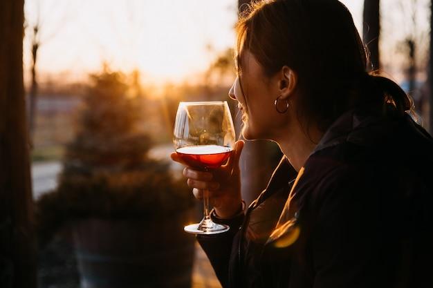 Junge frau, die ein glas rotwein im sonnenuntergangslicht draußen hält