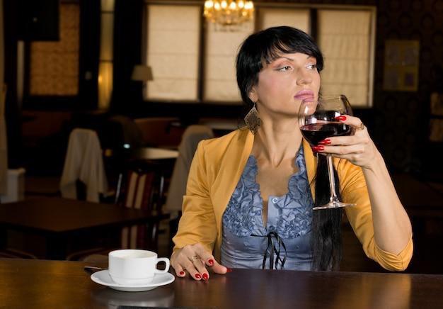 Junge frau, die ein großes glas rotwein und eine tasse espressokaffee genießt
