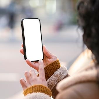 Junge frau, die ein leeres bildschirm-smartphone überprüft