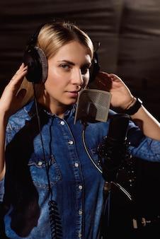 Junge frau, die ein lied im studio notiert