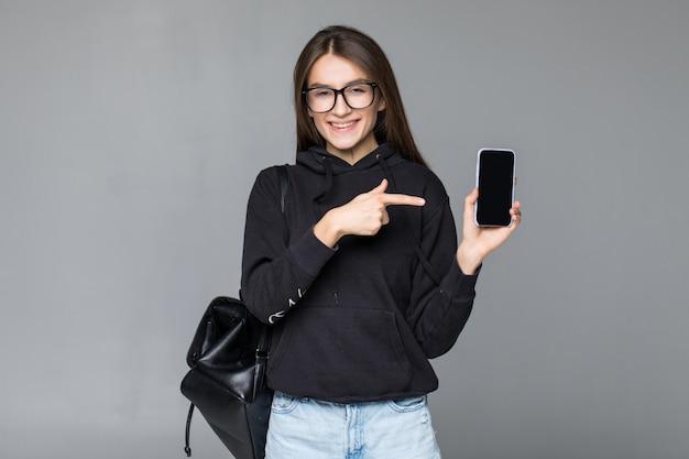 Junge frau, die ein mobiltelefon hält und auf es lokalisiert auf weißer wand zeigt