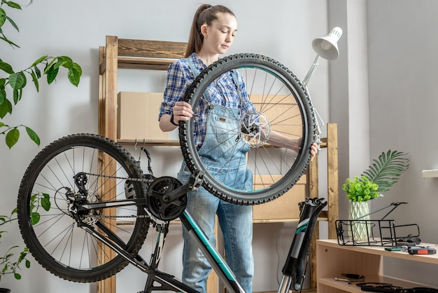 Junge frau, die ein mountainbike in einer werkstatt repariert. konzept der vorbereitung auf die neue saison, reparatur und wartung