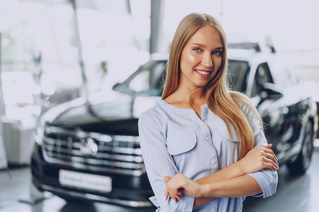 Junge frau, die ein neues auto auscheckt, das sie im autosalon kaufen wird