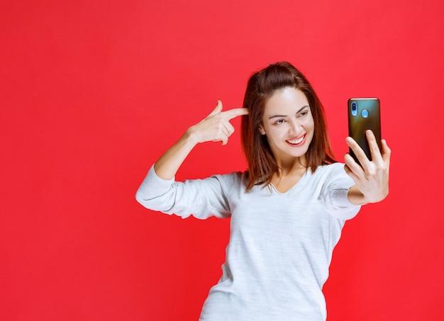 Junge frau, die ein neues schwarzes smartphone des modells hält und einen videoanruf macht oder ihr selfie nimmt