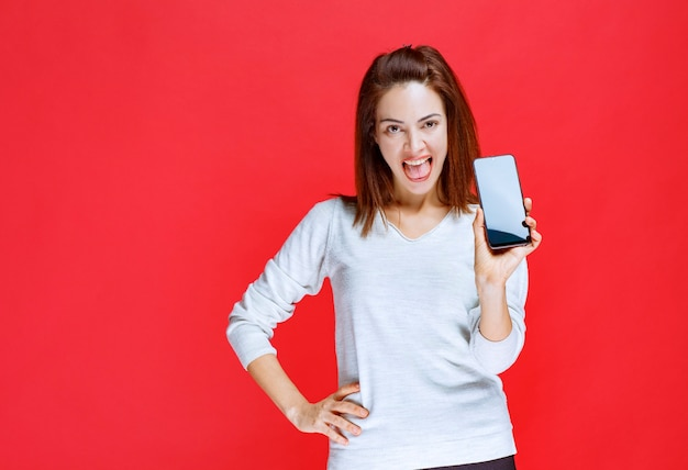 Junge frau, die ein neues schwarzes smartphone des modells hält und sich positiv und zufrieden fühlt