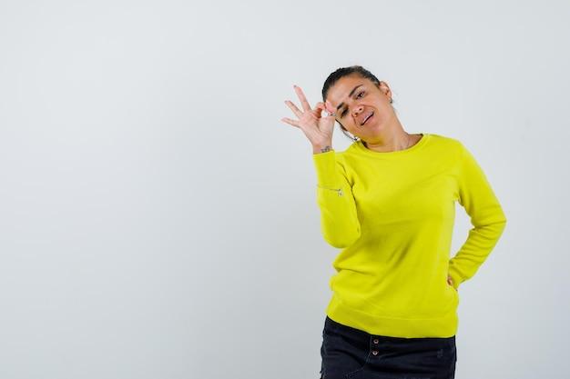 Junge frau, die ein ok-zeichen zeigt, während sie die hand in gelbem pullover und schwarzer hose hinter der taille hält und glücklich aussieht?