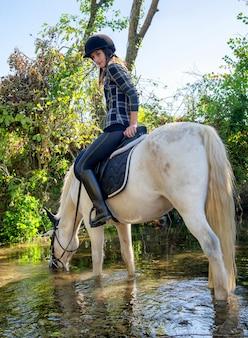 Junge frau, die ein pferd im fluss reitet ein schöner reiter und ein pferd.
