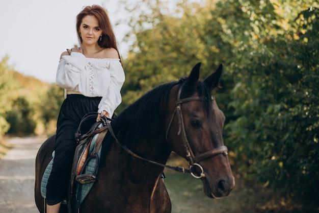 Junge frau, die ein pferd im wald reitet