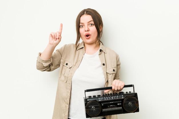 Junge frau, die ein retro-radio hält, das eine idee, inspirationskonzept hat.