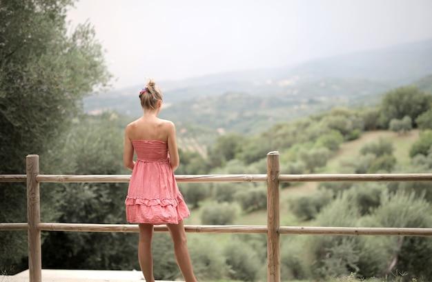 Junge frau, die ein rosa kleid mit einem wald trägt