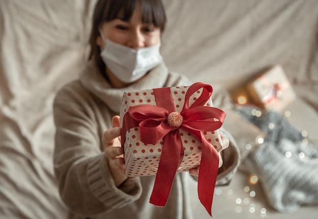 Junge frau, die ein schön verpacktes weihnachtsgeschenk hält. konzept des feierns von weihnachten während der coronavirus-pandemie.