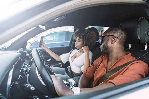 Junge frau, die ein selbstporträt mit ihrem freund in einem auto nimmt