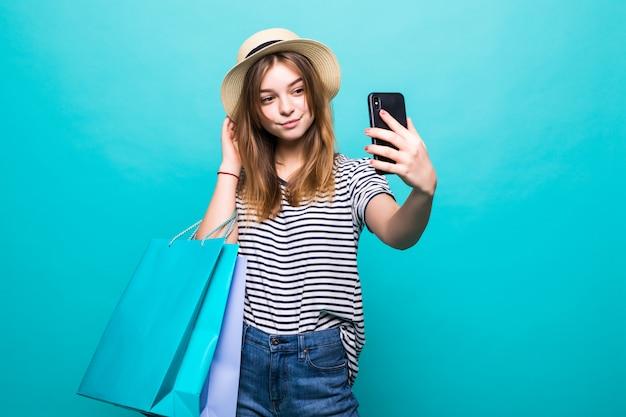 Junge frau, die ein selfie auf ihrem smartphone macht, das mit farbigen taschen zum einkaufen sitzt