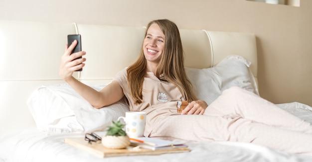 Junge frau, die ein selfie auf smartphone nimmt, während auf bett sitzend
