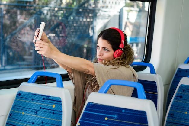 Junge frau, die ein selfie auf zug mit ihrem telefon nimmt.