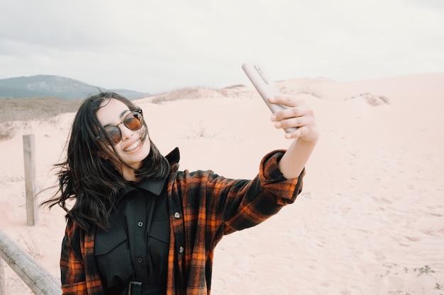 Junge frau, die ein selfie nimmt, das an den dünen lächelt