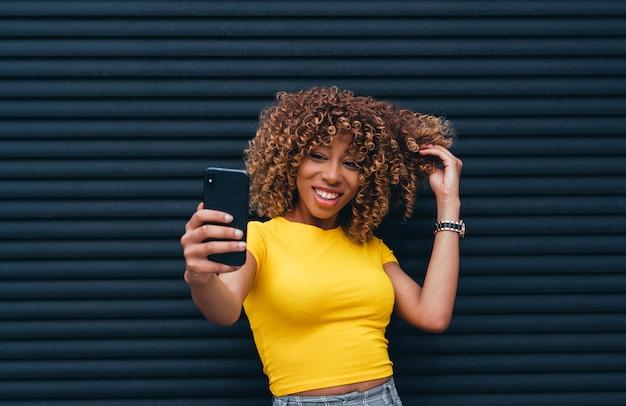 Junge frau, die ein selfie vorführt ihr fantastisches gelocktes haar nimmt.