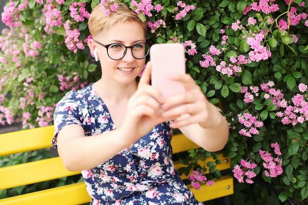 Junge frau, die ein smartphone nahe einem blumenbusch benutzt