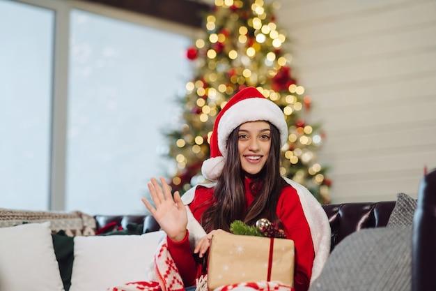 Junge frau, die ein weihnachtsgeschenk am silvesterabend hält