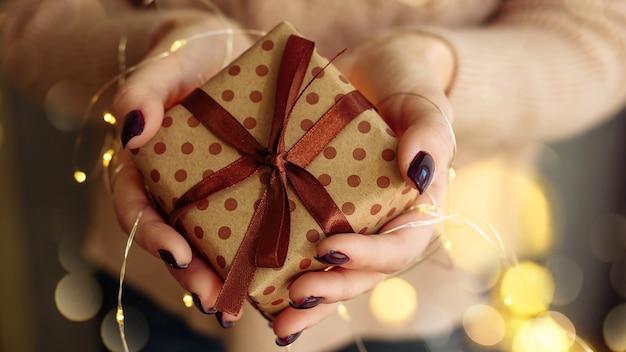 Junge frau, die ein weihnachtsgeschenk mit girlandenlichtern hält