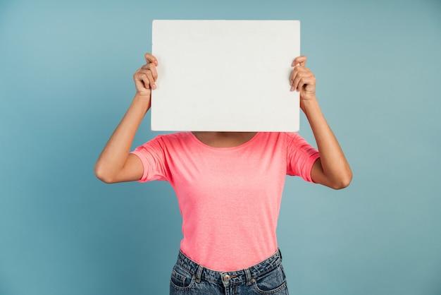 Junge frau, die ein weißes, leeres blatt papier hält. mädchen bedeckte ihr gesicht mit weißem papier