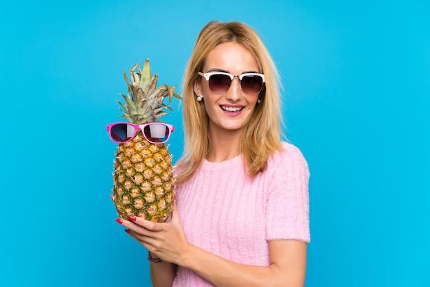 Junge frau, die eine ananas mit sonnenbrille hält